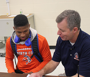 North Cobb staff member helping a male student in a long-sleeved orange shirt