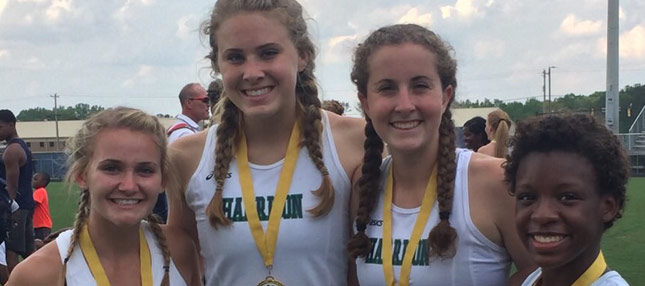 Four girls from track smiling