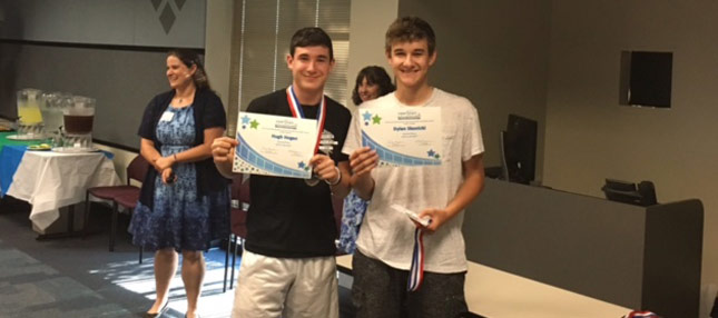 Two boys smiling with certificates
