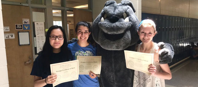 Students with certificates and the mascot
