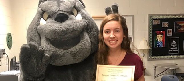 Student with certificate and the mascot
