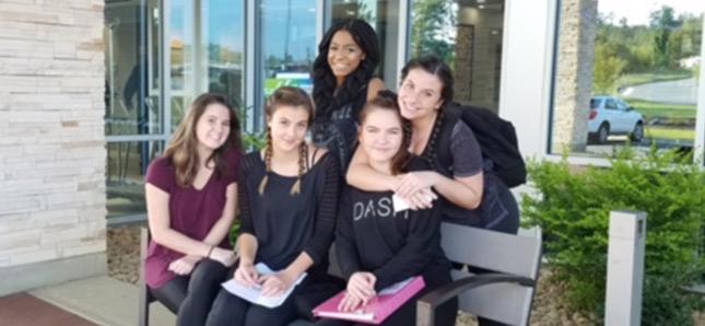 5 girls sitting on bench smiling