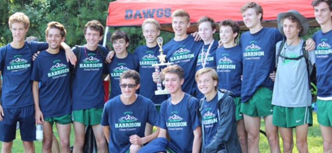 Group of boys huddled together holding trophy