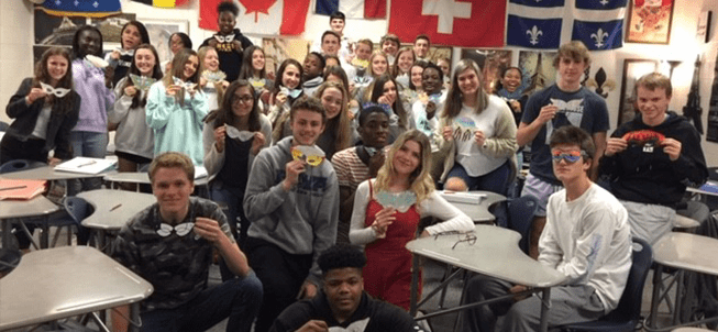 French Club pose and hold up their decorated masks in a classroom