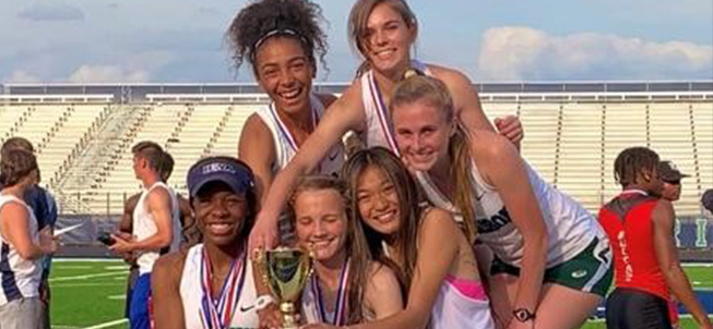 Six happy female track athletes posing with a trophy