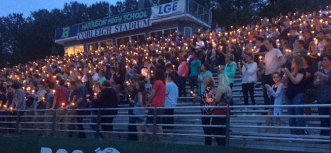 students with candles in stadium