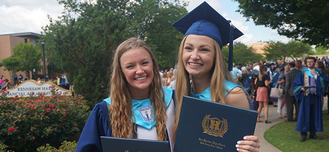 Smiling graduates hold up their diplomas
