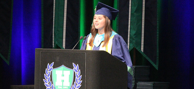 Harrison High graduate speaks from behind a podium during the graduation ceremony
