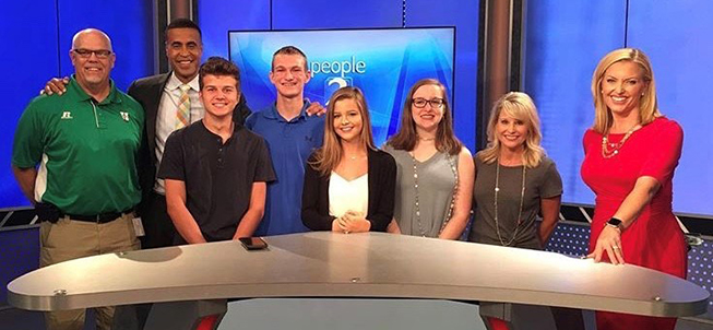 Group of Harrison High students pose with news anchors in a newsroom