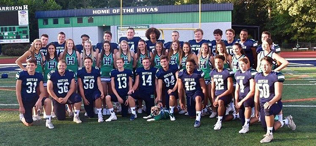 Harrison High football players and cheerleaders pose together on a field