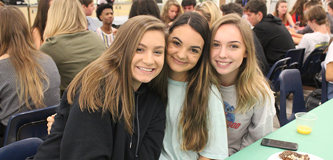 Three smiling girls pose together