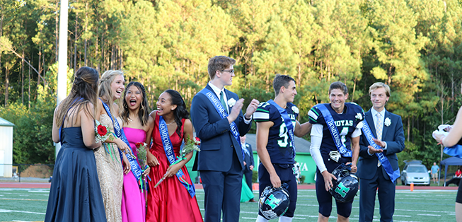 Homecoming court laughs and smiles together on a field