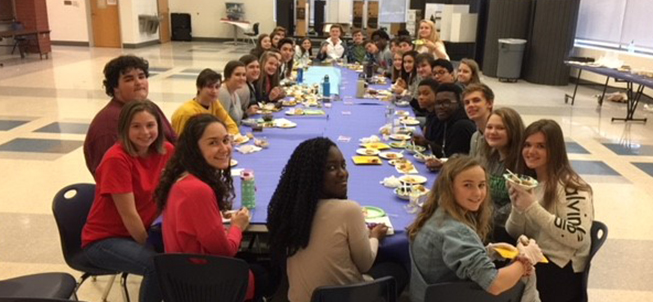 French club members enjoying a meal together at a long table