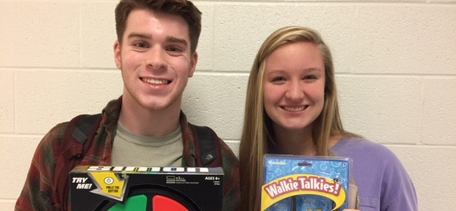 Two happy French club members holding up games