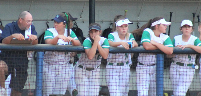 Softball team members leaning on a fence