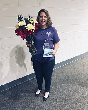 Rachel Sanford holds a vase of flowers and her award as teacher of the year