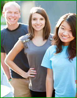 Three students pose together outside