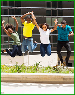 Four students jump in the air outside