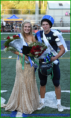 Homecoming Queen and King pose on a field