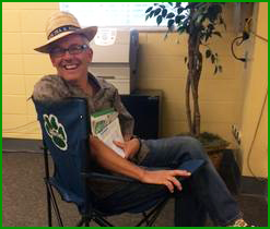 Smiling teacher sits in a folding chair