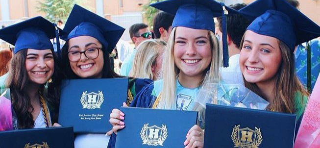 Four girl graduates smiling with diplomas