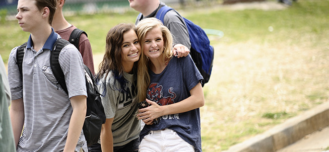 Two girls in a group of students hugging