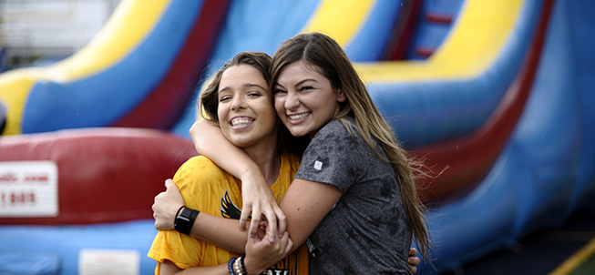 Two girls hugging in front of inflated slide
