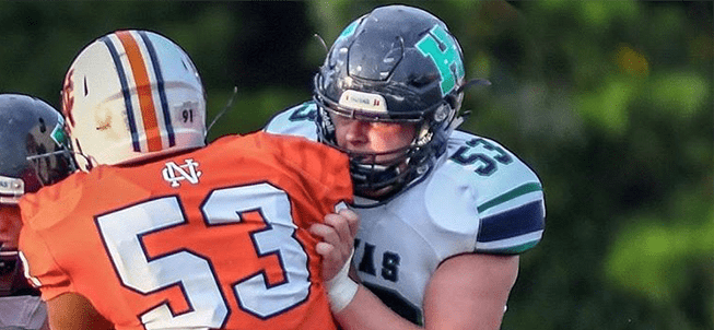 Two football players from opposing teams tackle each other