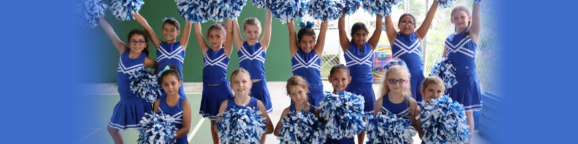 Smiling cheerleaders with pom poms