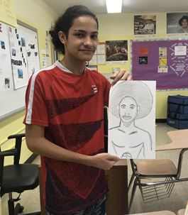 student holding up a pencil drawing