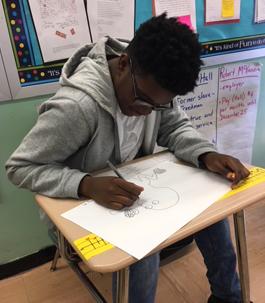 a boy drawing at his desk