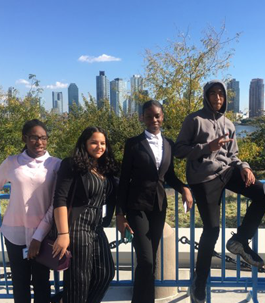 students dressed in business attire with the city skyline in the background