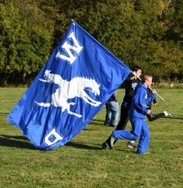 Blue Western Reserve flag being held by a man in blue suit during football game