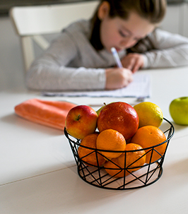 Elementary school girl sitting at kitchen table working on homework