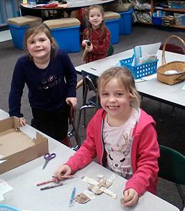 Three happy elementary school girls at their desk
