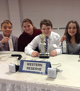 Happy middle school students sitting at a table with awards