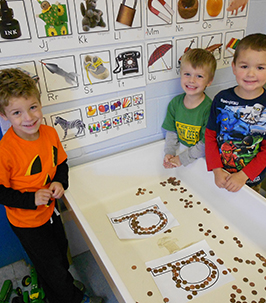 Three happy preschoolers in the classroom