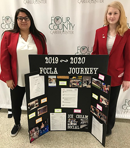 Two students posing with a 2019-2020 FCCLA Journey poster board