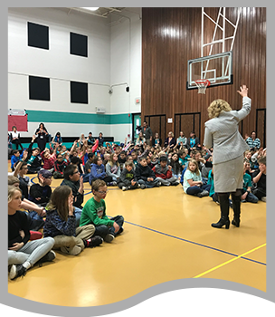 Teacher speaks to a group of students in a gym