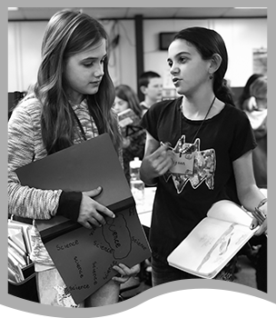 Two female students holding notebooks and talking to each other