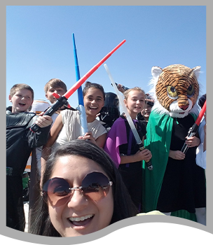 Teacher poses with students dressed as Star Wars characters and tigers with lightsabers