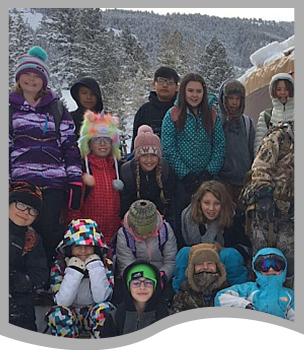 Students wearing winter attire pose together outside