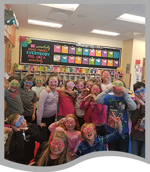 Students wear silly glasses and pose together