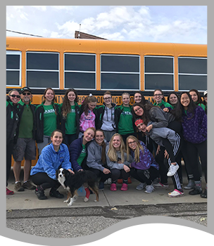 Group of students and a dog pose in front of a schoolbus