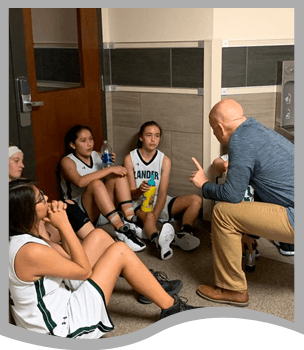 Coach talking to girls basketball players