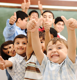 group of young children giving the thumbs up