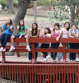 girls sitting on a bridge