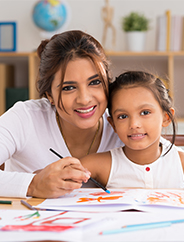 A happy mother helping daughter with schoolwork