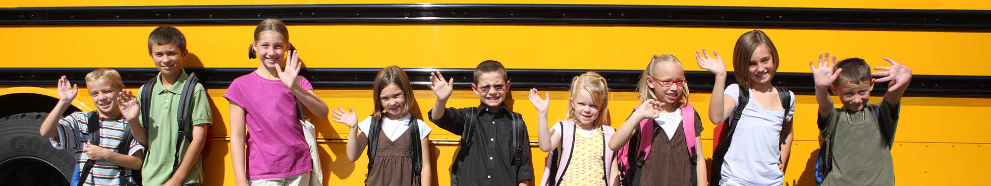 group of students in front of school bus