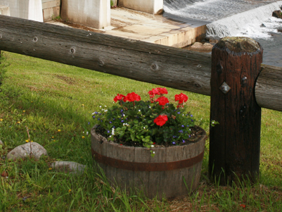 fence post with a basket of flowers sitting in the grass